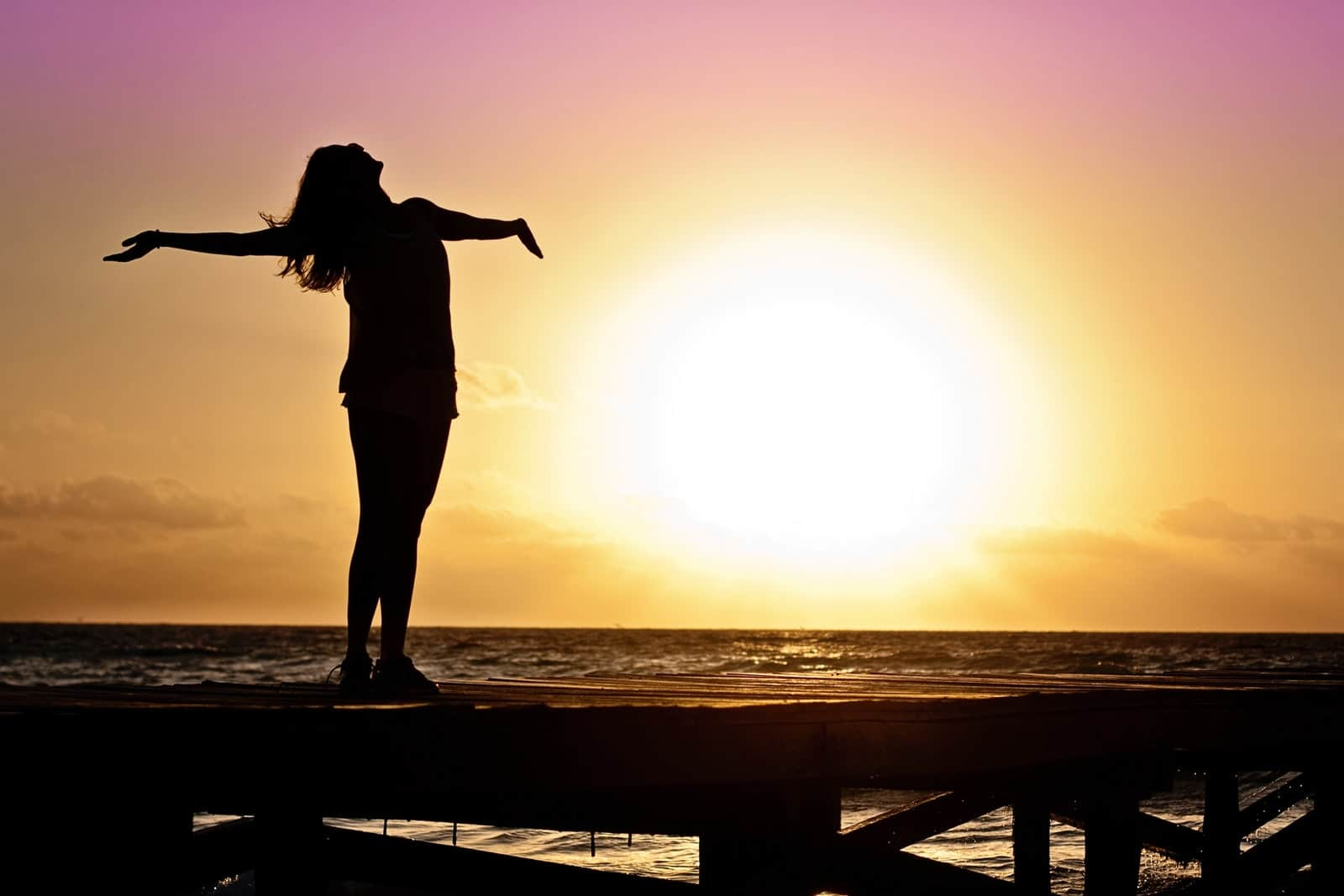 a woman standing arms outstretched toward the sunset symbolizing freedom from energy vampires